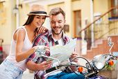 stock photo of scooter  - Beautiful young loving couple sitting on scooter together and examining map while woman pointing it and smiling - JPG