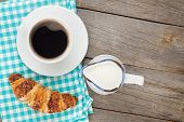 Cup of coffee, milk and fresh croissant on wooden table with copy space
