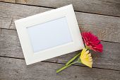 Two colorful gerbera flowers and photo frame on wooden table