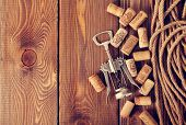 Wine corks and corkscrew over rustic wooden table background with copy space. Retro toned