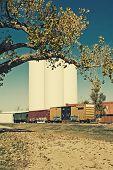 Rail cars sitting on a siding beside grain silos.