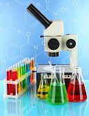 Test tubes with colorful liquids and microscope on blue background