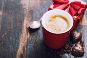 Valentine's day composition with coffee cup and chocolate on wooden background