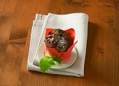 dark chocolate cupcake, served on the plate with fabric linen
