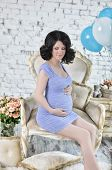 Pregnant woman with blue and white balloons