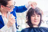 image of hairspray  - Female coiffeur giving women hairstyling with hairspray in hairdresser shop - JPG