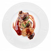 Venison fillet fried with pine nuts, served with sweet sauce, isolated