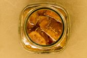 A glass jar containing chopped pieces of golden apple fruit dipped in sugar syrup