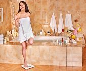Happy woman weighed on floor scales. Girl in bright towel