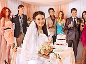 Group people at wedding table with cake. Bride with a bouquet of flowers in the foreground