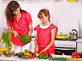 Mother and daughter cooking food at kitchen.A lot of vegetables and herbs on table