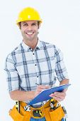 Portrait of happy male architect writing notes on clip board over white background
