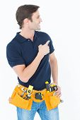 Happy man with tool belt around waist pointing against white background