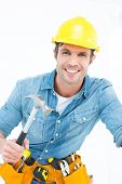 Portrait of confident carpenter using hammer against white background