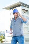 Portrait of male architect with blueprints using mobile phone outside building