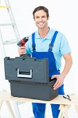 Portrait of happy carpenter removing drill machine from tool box over white background