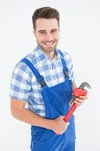 Portrait of confident young male repairman holding adjustable pliers on white background