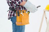 Side view of male repairman wearing glove while holding pliers on white background