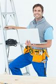 Portrait of confident electrician holding laptop by step ladder over white background