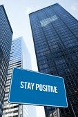 The word stay positive and blue billboard against low angle view of skyscrapers