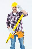 Portrait of confident handyman holding spirit level on white background