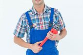 Cropped image of plumber holding monkey wrench over white background