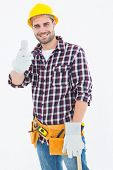 Portrait of happy male repairman gesturing thumbs up on white background