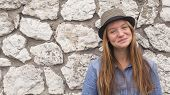 Cute teen girl on the stone wall background.