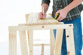 Cropped image of worker using measure tape to mark on wooden plank against white background