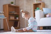 Little girl with digital tablet sitting on the floor