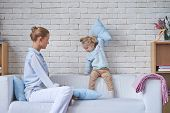 Pretty young woman sitting with cute child at home