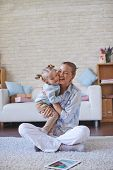 Happy woman playing with her daughter at home