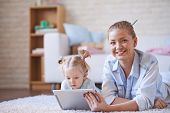 Cute little girl and her mother spending weekend with digital tablet at home
