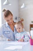 Little girl drawing with crayons with her mother near by