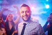 Handsome guy looking at camera at disco while his friends dancing on background