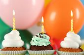 Delicious birthday cupcakes on bright background