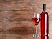 Red wine on table on wooden background
