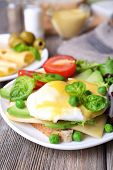 stock photo of benediction  - Toast with egg Benedict and avocado on plate on wooden table - JPG