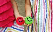 stock photo of bouncing  - Hands of two little girls holding colorful smiley face bouncing balls - JPG