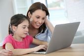 Mother and daughter doing homework on laptop