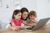 Mother with kids playing on laptop computer