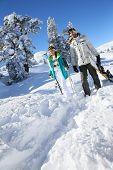 Skiers walking in snow track