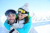 Man giving piggyback ride to girlfriend in snowy mountain