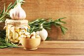 Canned garlic in glass jar on wooden background