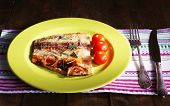 Dish of Pangasius fillet with rosemary and cherry tomatoes in plate on wooden table background