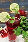 Pomegranate drink in glasses with mint and slices of lime on plate and color wooden background