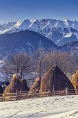 stock photo of haystack  - Winter rural landscape with traditional Romanian farm with sheep pen and haystacks near Piatra Craiului massif in Magura village Brasov county Romania - JPG