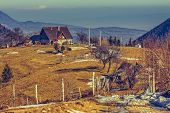 stock photo of household farm  - Peaceful Romanian rural scene with traditional farm and grassland uphill in Moeciu Brasov county Trasylvania region Romania - JPG