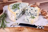 Blue cheese with sprigs of rosemary and nuts on board with knife and wooden table background