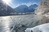 ice waves at austrian lake in winter mountain landscape